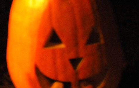 A pumpkin is  placed on the sidewalk in front of one of the houses participating in Halloween. Many carved pumpkins can be seen on Halloween night, as it is one of the many traditions of  the holiday.