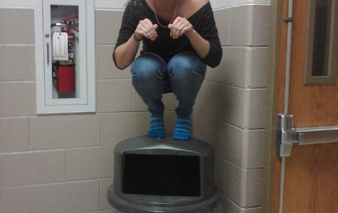"Sophomore Maddy Hoeft ""owl's"" on top of a garbage can in a Milford hallway. Photo by Sarah Schroeder"