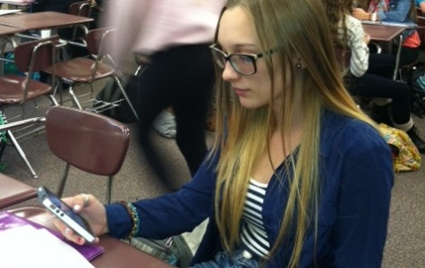 Junior Jordan Weinand uses her phone to read an article during class.  Once banned, cell phones are now allowed in many classes as the district sees the possibility of students bringing their own devices to work on class assignments.