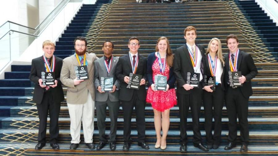 Eight students fro Milford High School hold State Champion plaques.