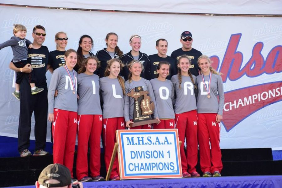 Milford girls cross country team gather on stage to accept the trophy