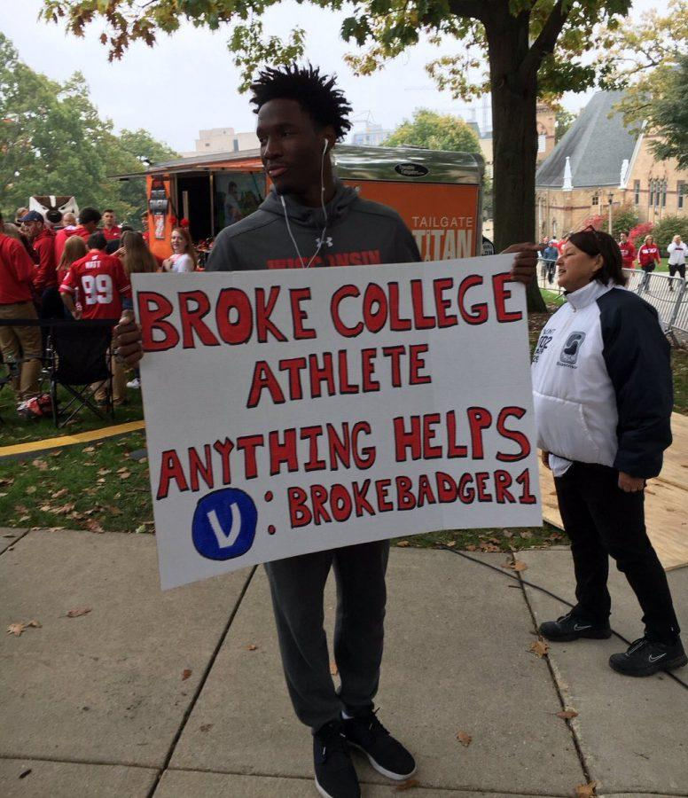 Nigel+Hayes%2C+a+University+of+Wisconsin+basketball+player%2C+holds+a+sign+protesting+the+NCAA+at+College+Gameday.