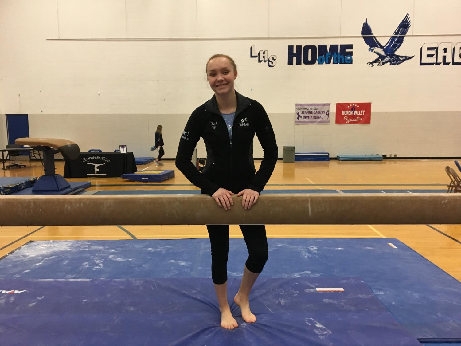 Ciara Charlick poses behind the beam at the 2018  Jeanne           Caruss Invitational, one year after her injury. (Photo by Maddie Kobylski)