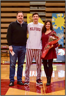 Senior Aiden Warzecha stands with his parents while being honored on Senior Night
