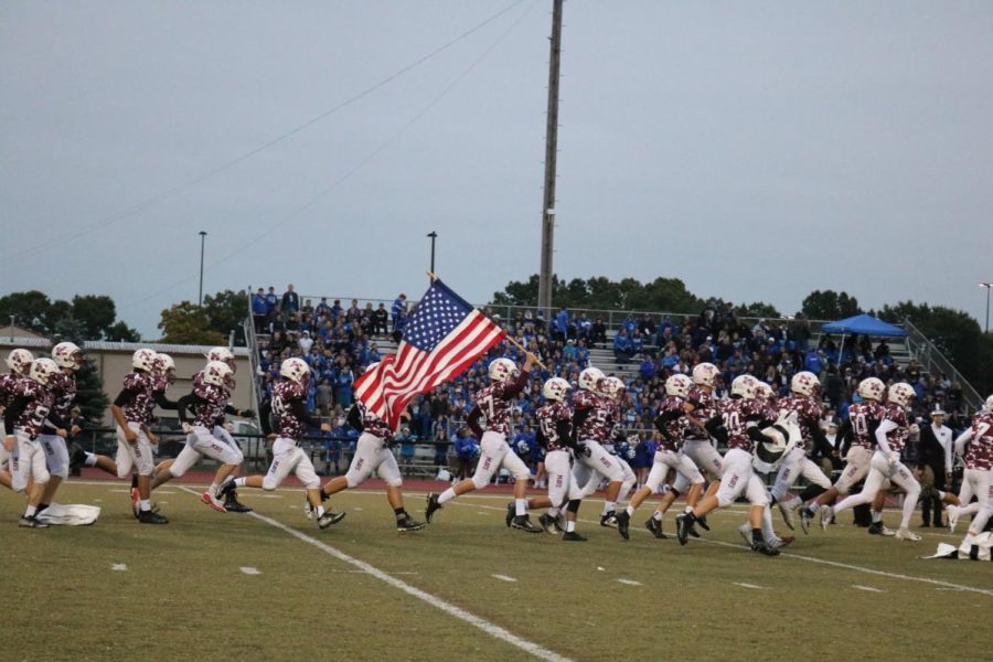 The+Varsity+Football+Team+runs+onto+the+field+Lead+by+Jake+Miller+holding+up+the+flag.+%28All+photos+courtesy+of+Jerry+Rea%29%0A