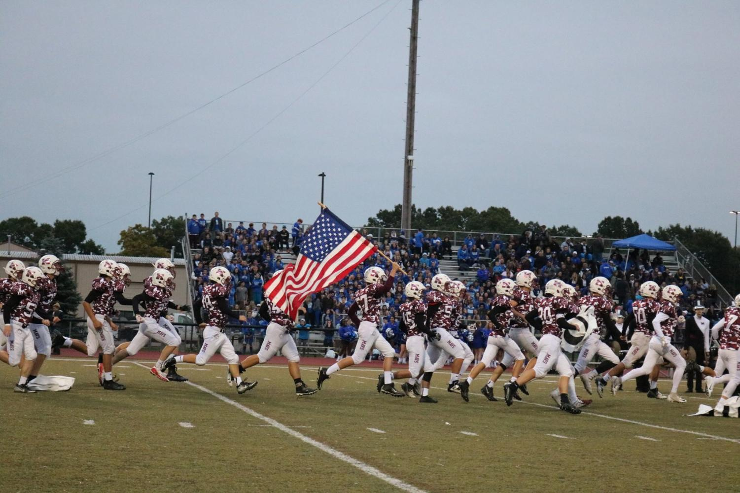 The Varsity Football Team runs onto the field Lead by Jake Miller holding up the flag. (All photos courtesy of Jerry Rea)