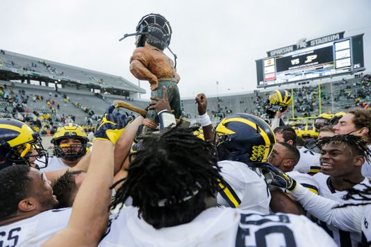 Michigan Wolverines celebrating with the Paul Bunyan Trophy, courtesy of Detroit Free Press