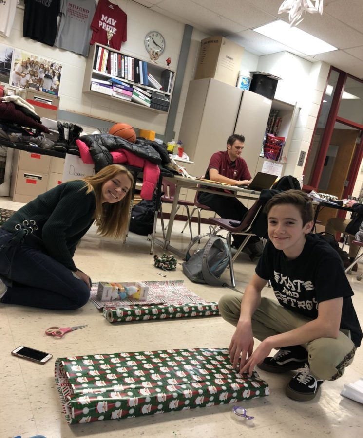 Senior+Hailey+Phipps+%28left%29+and+sophomore+Aidan+Wilson+%28right%29+wrapping+gifts+they+bought+for+their+designated+Milford+Miracles+family.+%28Photo+by+Abby+Knapp%29%0A