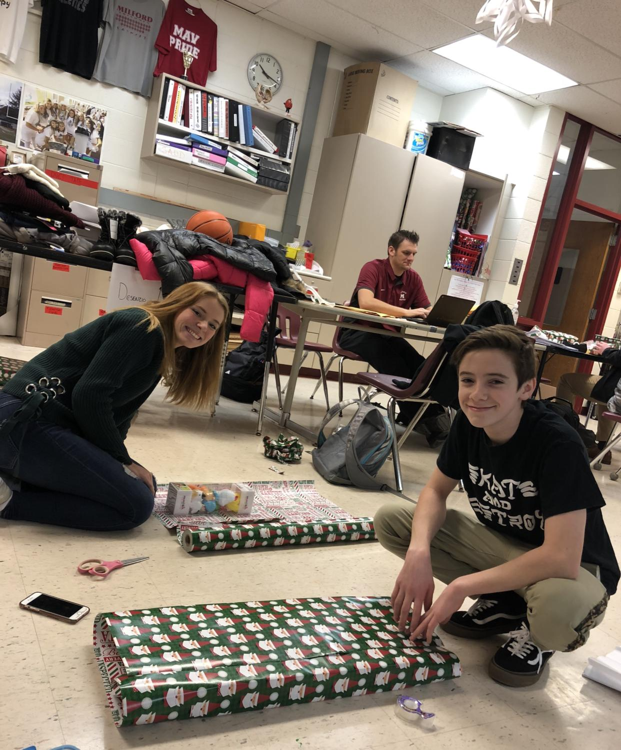 Senior Hailey Phipps (left) and sophomore Aidan Wilson (right) wrapping gifts they bought for their designated Milford Miracles family. (Photo by Abby Knapp)