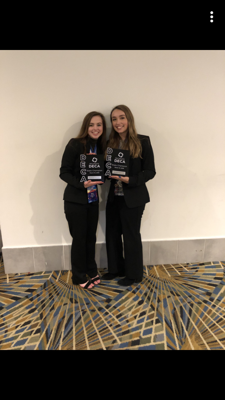 DECA members Anna Fischer along with Alexis Camilleri holding their state champion plaque.
