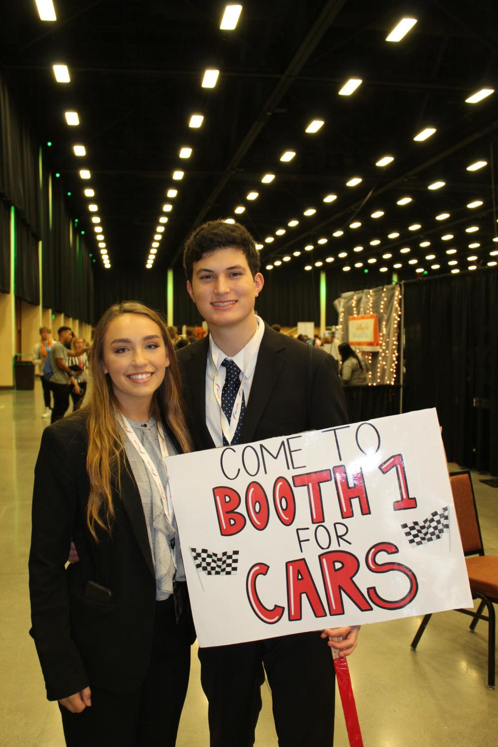 Seniors Alexis Camilleri and Austin Maiberger advertising the cars on a poster Austin drew.