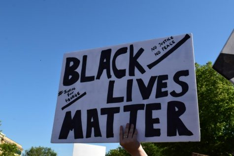 A person at the Black Lives Matter protest in Milford, MI holds up a homemade sign.