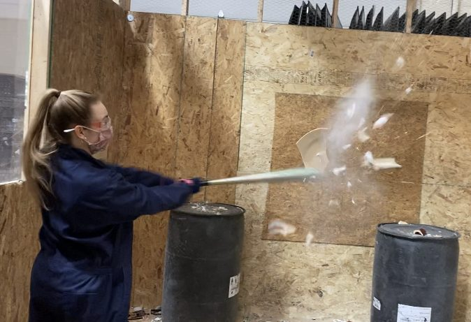 Senior Claire Adams breaks a plate in mid-air at the rage room.
