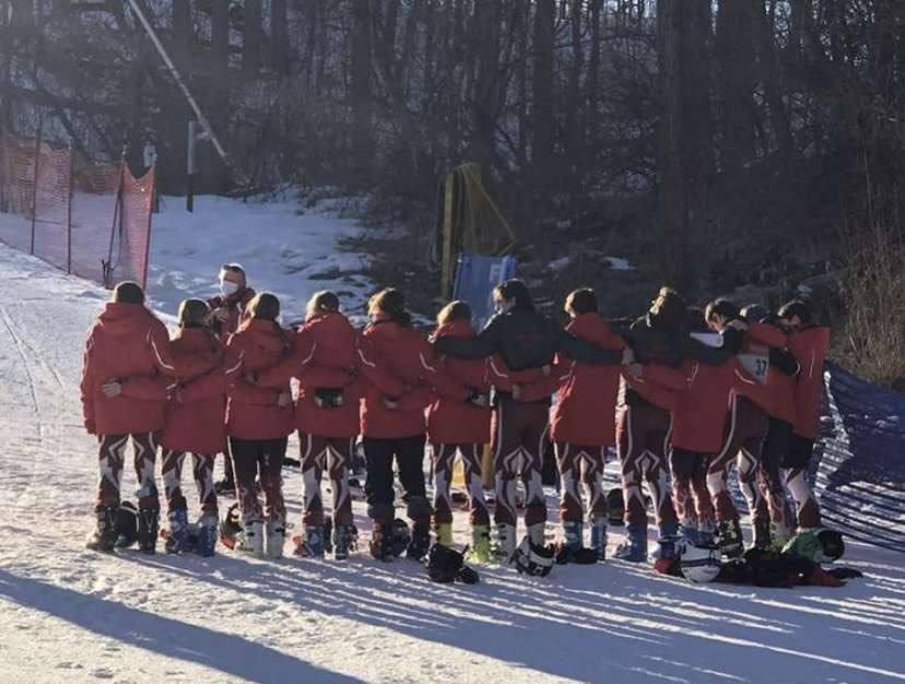 Boys and girls ski teams arm-in-arm before a run.
