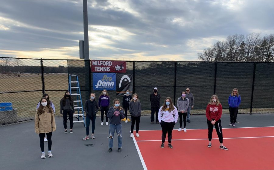 The girls putting up windscreens on the courts in preparation for their season.