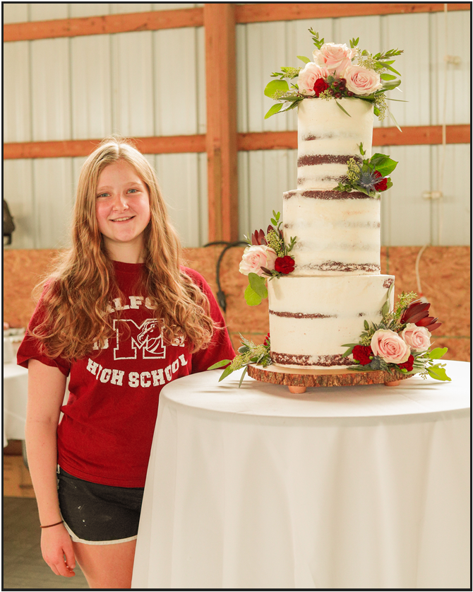 Kennedy Russell standing next to one of her wedding cakes (Photo courtesy of Kennedy Russell)